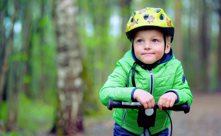 Dziecko na rowerze w kasku na głowie