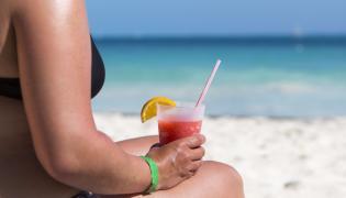 Kobieta na plaży pije zimny napój