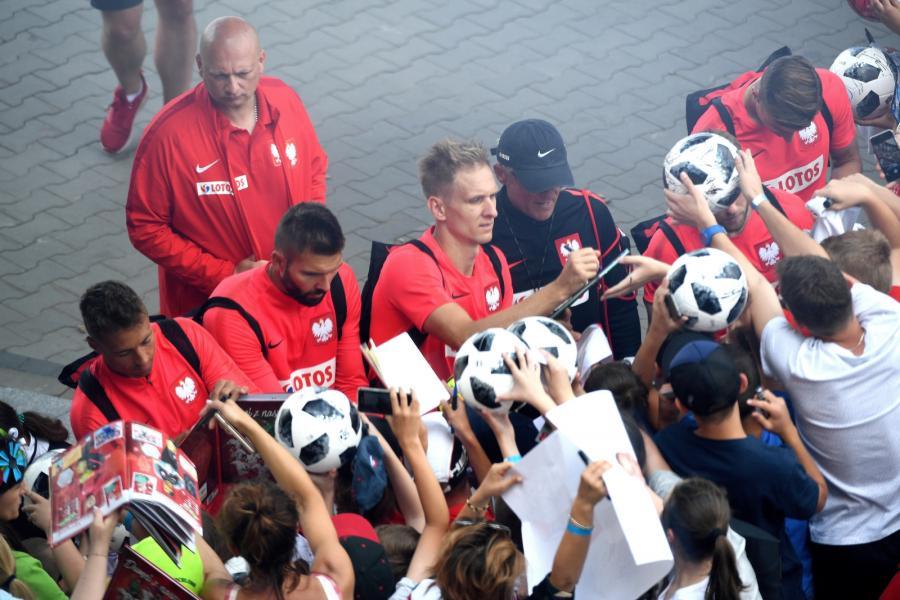 Zawodnicy piłkarskiej reprezentacji Polski rozdają autografy
