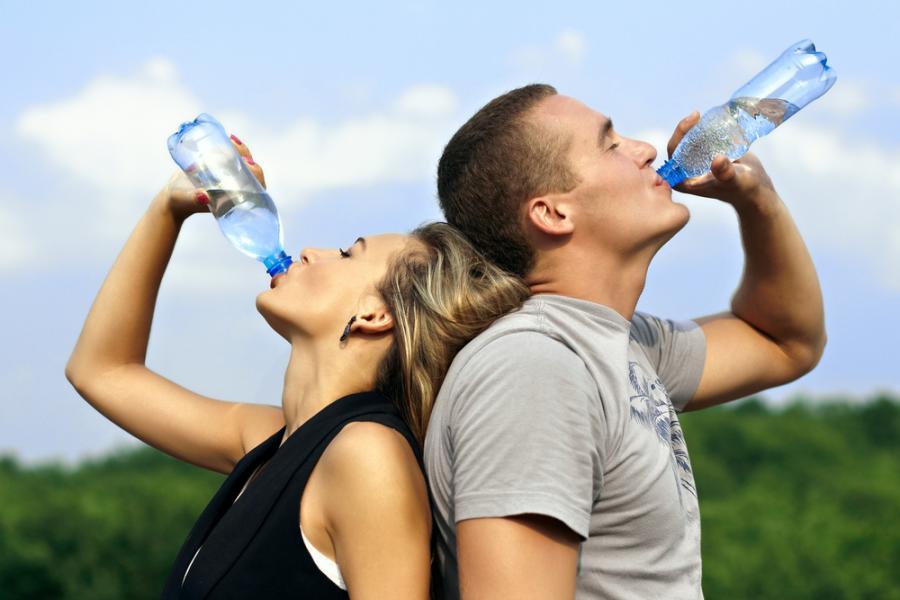 Kobieta i mężczyzna na treningu piją wodę