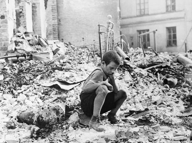 Warszawa wrzesień 1939, mały chłopiec w przerwie pomiędzy nalotami siedzi na ruinach swojego domu zbombardowanego przez nimieckie lotnictwo