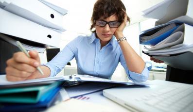 Kobieta wśród sterty dokumentów