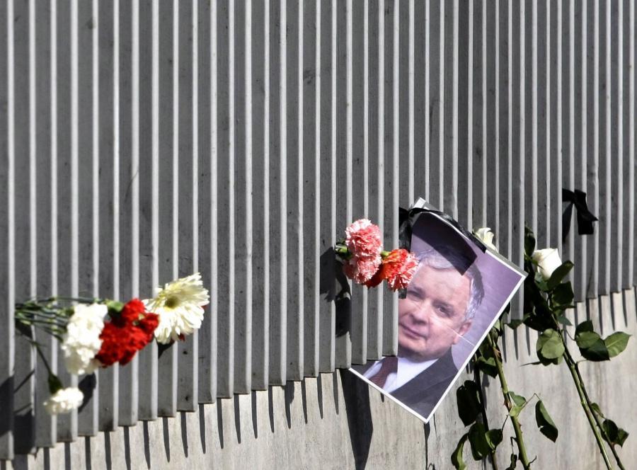 Zdjęcie Lecha Kaczyńskiego wśród kwiatów na ogrodzeniu polskiej ambasady w Moskwie po katastrofie smoleńskiej