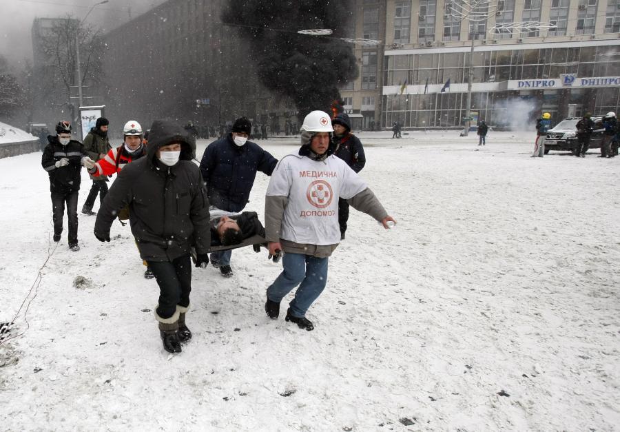 Demonstranci niosą rannego w czasie starć na Majdanie