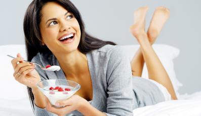 Kobieta je jogurt z malinami