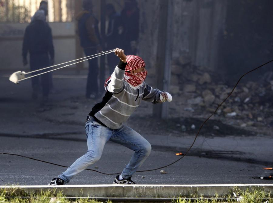 Młody Palestyńczyk miota kamieniem w izraelskich żołnierzy