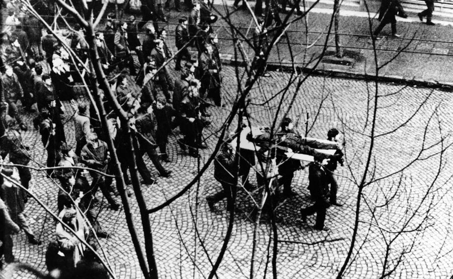Gdynia. 17 grudnia 1970 roku. Ulicą Świętojańską demonstranci niosą na drzwiach zwłoki Zbigniewa Godlewskiego, który zginął w okolicy przystanku Szybkiej Kolei Miejskiej Gdynia Stocznia