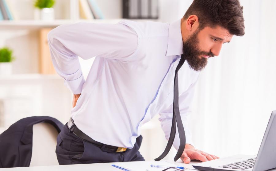 Mężczyzna wstaje zza biurka z bólem pleców