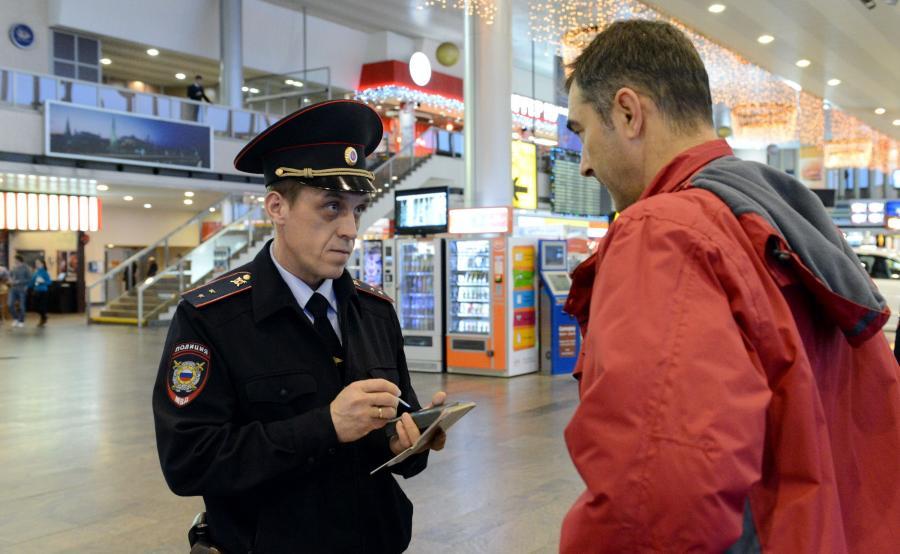 Rosyjski policjant kontroluje mężczyznę na moskiewskim lotnisku