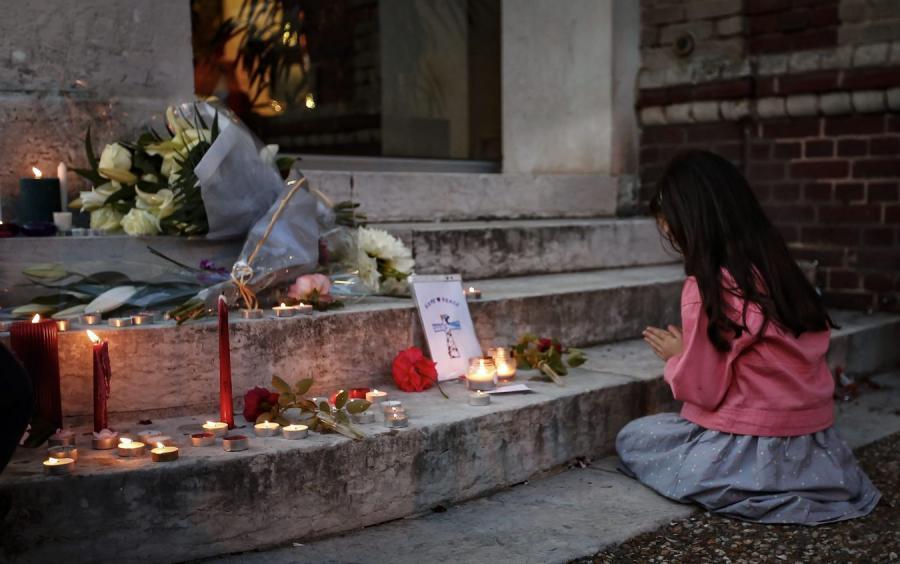 Dziewczynka modli się przed wejściem do kościoła w Saint-Etienne-du-Rouvray