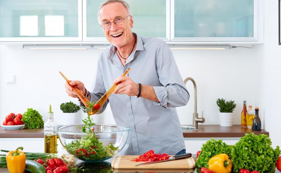 Starszy mężczyzna przygotowuje sałatkę