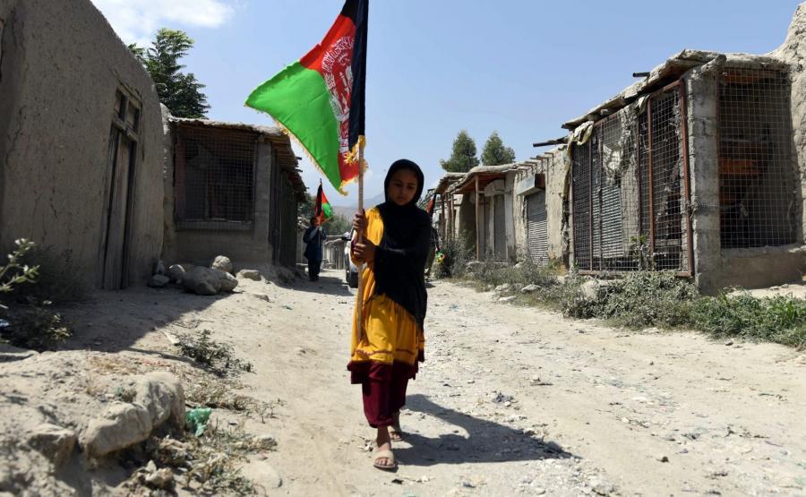 Aganistan. Kobieta niesie afgańską flagę wśród zabudowań odbitych z rąk bojowników z Państwa Islamskiego w prowincji Nangarhar