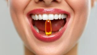 Kobieta trzyma w zębach kapsułkę